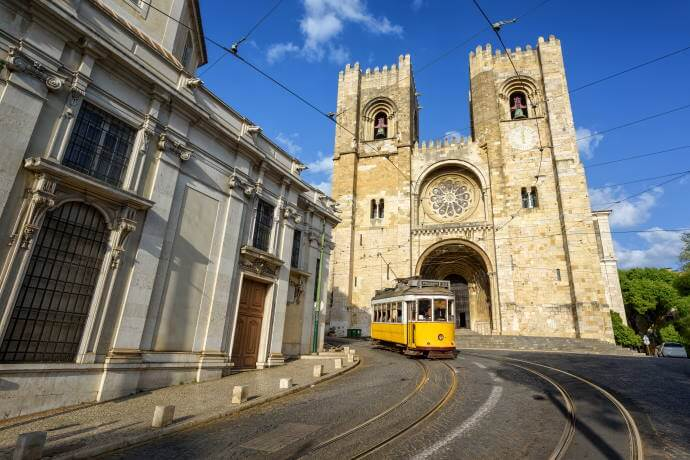 Old tram in front of cathedral in Lisbon